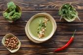 pohled shora uspořádány Vegetariánská krémová polévka, klíčky, mandle, čerstvá brokolice v miskách a chilli papričkami na dřevěný povrch