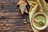 Fotografie top view of arrangement of vegetarian cream soup with sprouts, pieces of bread and almonds on wooden surface