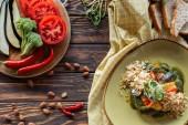 plochý ležel s vegetariánský salát, mandle, chilli papričky, čerstvou zeleninou a kousky chleba na dřevěnou desku