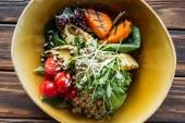 pohled shora na vegetariánský salát s grilovanou zeleninou, kapusta, rajčata cherry v misce na dřevěnou desku