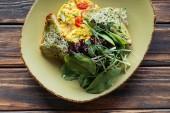 pohled shora vegetariánský salát s listovým špenátem a klíčky na štítku na dřevěnou desku