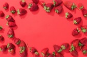 Frame of raw juicy strawberries on red background