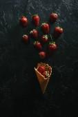 pohled shora červené jahody v oplatkovém kornoutku na tmavém pozadí