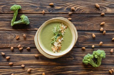 flat lay with arranged fresh broccoli, almonds and vegetarian cream soup on wooden tabletop