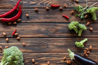 top view of arranged fresh vegetables, chili peppers and almonds on wooden surface