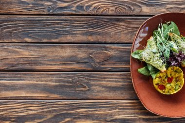 top view of vegetarian salad with sprouts and spinach on plate on wooden surface