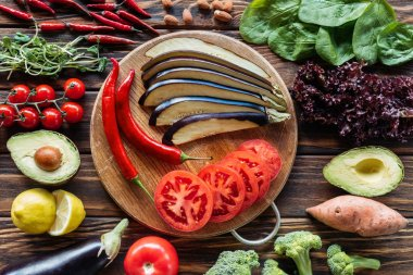 flat lay with cut eggplant, tomatoes and chili peppers on cutting board with fresh vegetables around on wooden surface