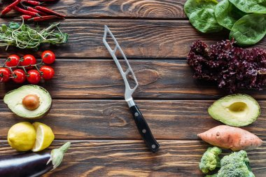 top view of arranged fresh vegetables and knife on wooden tabletop
