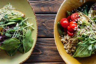 flat lay with vegetarian salads with spinach and sprouts served in bowls on wooden tabletop