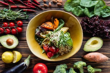 flat lay with vegetarian salad with grilled vegetables, sprouts, cherry tomatoes in bowl and arranged fresh ingredients around on wooden tabletop