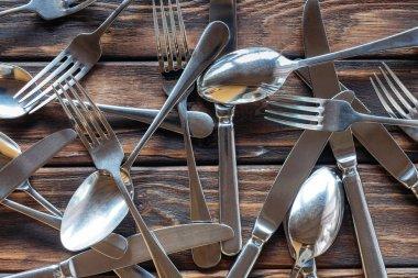 full frame of arranged steel cutlery on wooden tabletop