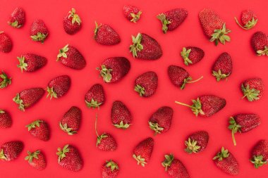 top view of raw strawberries isolated on red background