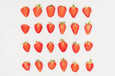Rows of cut strawberries isolated on white background