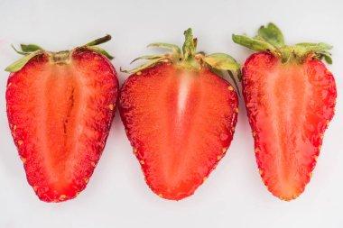 Three halves of strawberries on white background