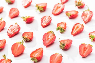 red fresh cut strawberries on white background