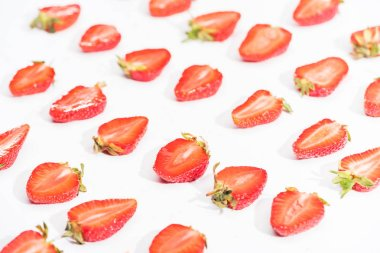 Fresh cut strawberries in rows on white background
