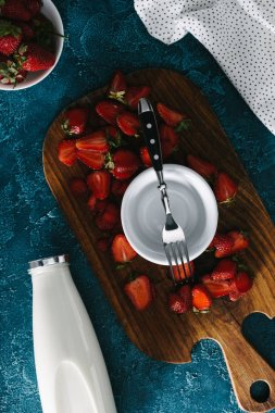 top view of bowl with fork by ripe strawberries and milk bottle on table