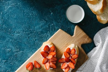 Wooden board with strawberry sandwiches on blue table