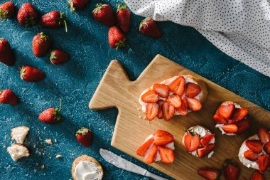 top view of bread with cream cheese and strawberries on wooden cutting board