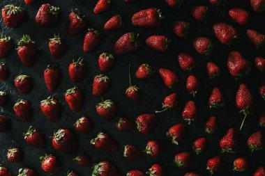 Spiral composition of red strawberries on dark background