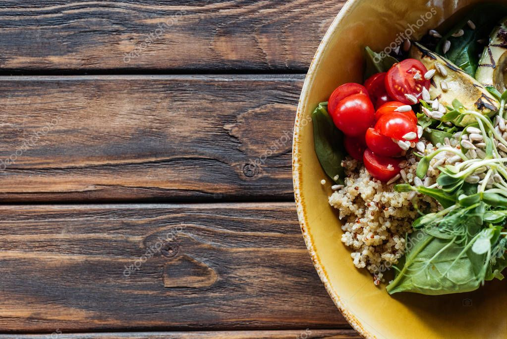 top view of vegetarian salad with grilled vegetables, sprouts, cherry tomatoes in bowl on wooden tabletop