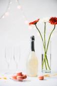 Nahaufnahme von Macarons, leeren Gläsern, einer Flasche Champagner und einem Strauß Gerbera-Blumen vor grauem Hintergrund