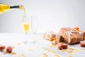 Fotografie Nahaufnahme strömenden gelbe Champagner Gläser Prozess, Macarons und arrangierte Geschenke auf grauem Hintergrund