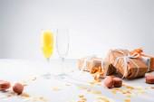 Fotografie Nahaufnahme von Glaswaren mit gelben Champagner, Macarons und arrangierte Geschenke auf grauem Hintergrund