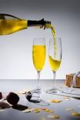 Fotografie Nahaufnahme strömenden gelbe Champagner in Glaswaren und arrangierte Geschenke auf grauem Hintergrund