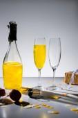 Fotografie Nahaufnahme von Glaswaren mit gelben Champagner und verpacktes Geschenk auf grauem Hintergrund