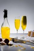 Fotografie Nahaufnahme von Glaswaren mit gelben Champagner und Geschenk auf grauem Hintergrund