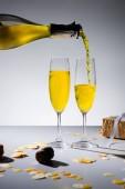 Fotografie Nahaufnahme strömenden gelbe Champagner in Gläser und verpacktes Geschenk auf grauem Hintergrund