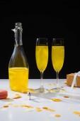 Fotografia Chiuda sulla vista della bottiglia e bicchieri di champagne giallo, macaron e regalo sulla superficie su priorità bassa nera