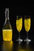 Fotografia Chiuda sulla vista della bottiglia e bicchieri di champagne giallo su sfondo nero