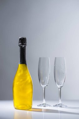 close up view of bottle of champagne and empty glasses on grey background