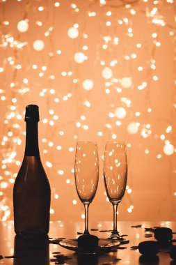 close up view of bottle of champagne and empty glasses in bokeh style