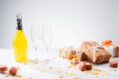 close up view of bottle of yellow champagne, empty glasses, macarons and arranged gifts on grey backdrop