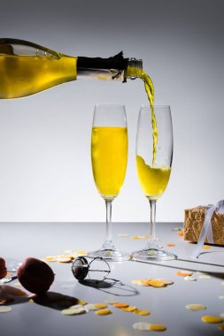 close up view of pouring yellow champagne into glassware process and arranged gifts on grey backdrop