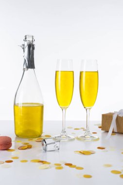 close up view of bottle and glasses with yellow champagne and wrapped gift on grey backdrop