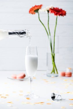 selective focus of pouring champagne into glass process, macarons and bouquet of flowers on grey background