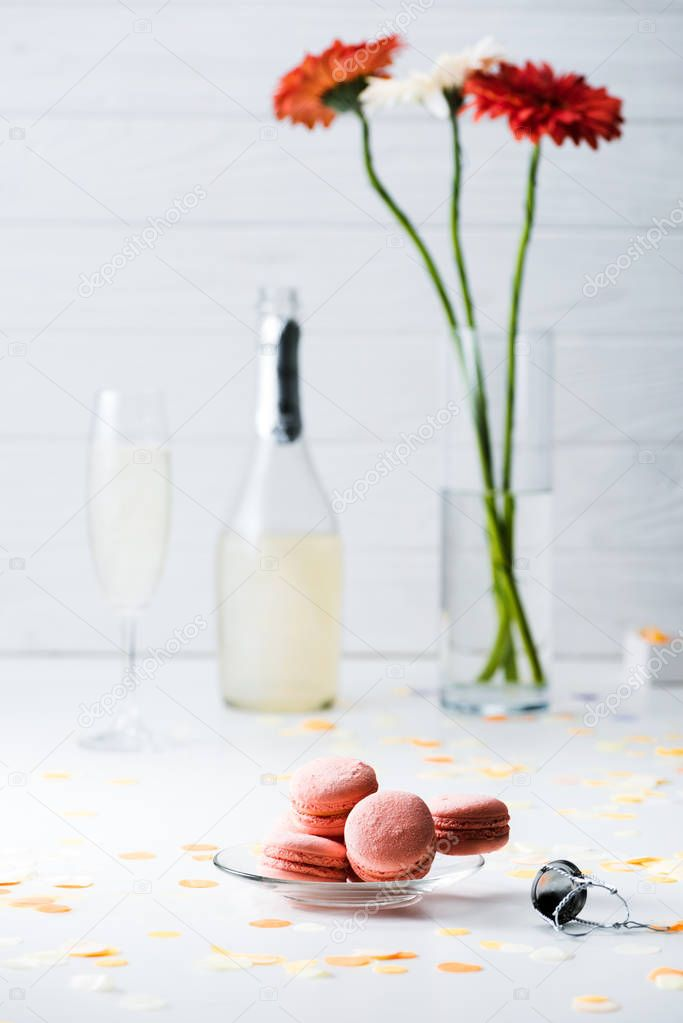 selective focus of sweet macarons, bottle and glass of champagne, bouquet of gerbera flowers on grey background