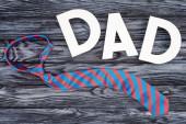 pohled shora kravatu s tátou nápisy na šedý dřevěný stolní, šťastný otcové den koncept