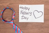 top view of vivid tie with Happy fathers day greeting card on wooden surface