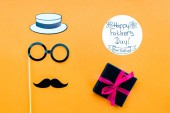 Fotografie Draufsicht der Gentleman Gesicht glücklich Väter Tag Grußkarte mit Geschenk auf gelbe Fläche