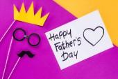 Fotografia vista superiore di re viso con scatola regalo con biglietto di auguri di giorno di padri felice su superficie variopinta