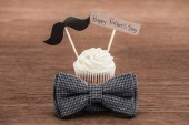 chutné košíčky s knírkem znak, motýlek a Happy fathers den nápis na dřevěný povrch