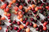 top view of fresh ripe organic cherries on marble surface