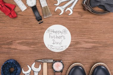 top view of Happy father's day greeting card surrounded with fathers attribution on wooden surface