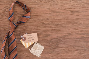 top view of tie with gifts and Happy fathers day greeting on wooden tabeltop