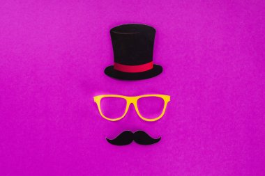top view of gentleman face made of cardboard eyeglasses, mustache and hat on pink surface